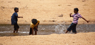 Tre srilankesiska pojkar som leker i en strömma Royaltyfria Bilder