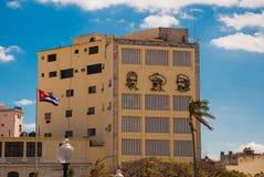 Tre stående är på väggen av byggnaden: Che Guevara Fidel Castro Den kubanska flaggan framkallar cuba havana Arkivfoton