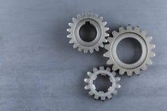 Tre stålkugghjul på en stålbakgrund Arkivfoton