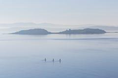 Tre stanno sui pensionanti della pagaia fuori in open water Fotografie Stock