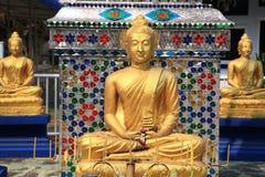 Tre statue dorate di Buddha al tempio tailandese Fotografia Stock