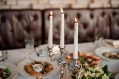 Tre stearinljus i den eleganta stearinljushållaren som dekorerar en tabell Royaltyfria Foton
