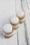 Tre stearinljus på den vita tabellen Royaltyfria Bilder