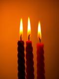 Tre stearinljus på guling Royaltyfri Fotografi