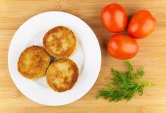 Tre stekte kotletter i platta, röda tomater och dill Arkivbilder