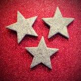 Tre stelle d'argento su struttura luccicante rossa Immagini Stock Libere da Diritti