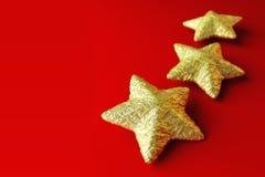 Tre stelle dorate su priorità bassa rossa Immagini Stock Libere da Diritti