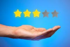 Tre stelle gialle dorate su cinque L'uomo tiene la stella sulla palma della sua mano, mette la valutazione, esami Fotografie Stock