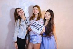 Tre stilfulla kvinnliga vänner som poserar med tecknet och kallar för sh Royaltyfri Fotografi