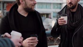 Tre stiliga män med skägg som har konversation och kaffe utanför Långsam mo