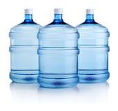 Tre stora flaskor av vatten som isoleras på vit bakgrund Fotografering för Bildbyråer