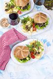 Tre stora hamburgare med sallad och potatisar glass rött vin smaklig matställe Skräpmat Text, Royaltyfria Bilder