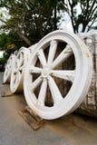 Tre stora hjul som göras av stenen, står mot väggen Royaltyfria Foton