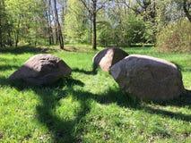 Tre stora stenblock i ängen Arkivbild