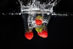 Tre strawberrys som plaskar in i vatten Royaltyfri Fotografi