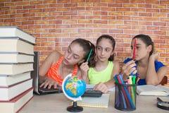 Tre studente, ragazza che lavora al suo compito Ritratto dello studente della High School delle ragazze che studia e che scrive Fotografie Stock Libere da Diritti