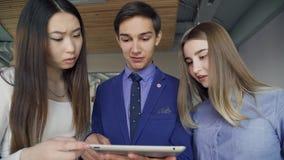 Tre studenter ser den vita minnestavlaskärmen som inomhus står arkivfilmer