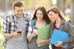 Tre studenter som kontrollerar smarta telefoner arkivfoto