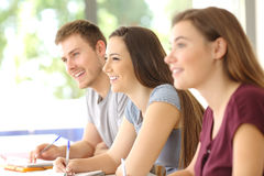 Tre studenter som lyssnar i ett klassrum Arkivbild