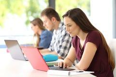 Tre studenter som studerar på linje i ett klassrum Royaltyfri Bild