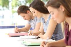 Tre studenter som tar anmärkningar under en grupp arkivbild