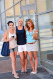 Tre studentflickavänner utanför att le för högskola Royaltyfri Bild