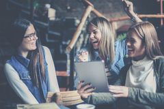 Tre studentflickor hemma som använder digital minnestavlatogeth arkivbilder
