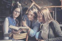 Tre studentflickor som tillsammans studerar Royaltyfri Fotografi