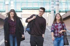 Tre studenti che camminano nella città universitaria Immagini Stock