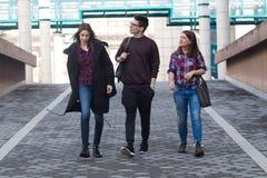 Tre studenti che camminano nella città universitaria Immagine Stock