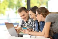 Tre studenti che imparano insieme sulla linea Fotografia Stock