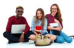 Tre studenti che si siedono con i libri, il computer portatile e le borse isolati su w Fotografie Stock Libere da Diritti