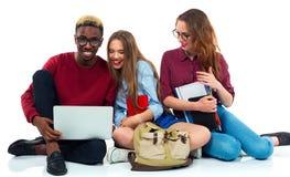 Tre studenti che si siedono con i libri, il computer portatile e le borse isolati su w Fotografia Stock