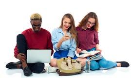 Tre studenti che si siedono con i libri, il computer portatile e le borse isolati su w Immagini Stock
