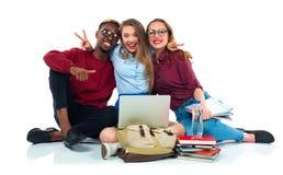 Tre studenti che si siedono con i libri, il computer portatile e le borse isolati su w Fotografia Stock Libera da Diritti