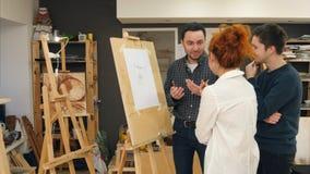 Tre studenti di arte allegri che discutono verniciatura nello studio immagini stock
