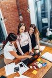 Tre studenti di college femminili che lavorano insieme all'assegnazione facendo uso del computer portatile che sta a casa fotografia stock