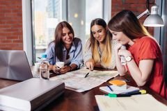Tre studenti di college femminili sorridenti che lavorano insieme al progetto nella biblioteca di scuola Fotografia Stock