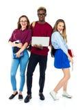 Tre studenti felici che stanno e che sorridono con i libri Immagine Stock Libera da Diritti