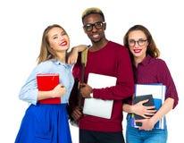 Tre studenti felici che stanno e che sorridono con i libri Fotografia Stock