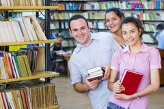Tre studenti in biblioteca fotografia stock libera da diritti