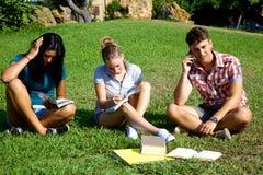 Tre studenti nel funzionamento del parco Immagini Stock Libere da Diritti