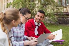 Tre studenti occupati che ritengono sovraccaricati facendo compito domestico Immagini Stock Libere da Diritti