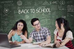 Tre studenti occupati nella classe Immagini Stock