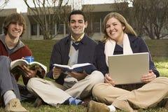 Tre studenti seduti all'aperto Fotografie Stock