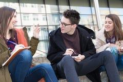 Tre studenti sorridenti felici stanno imparando Fotografie Stock Libere da Diritti