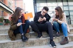 Tre studenti sorridenti felici stanno imparando nella città universitaria Fotografia Stock Libera da Diritti