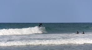 Tre surfisti sull'acqua durante l'addestramento fotografia stock