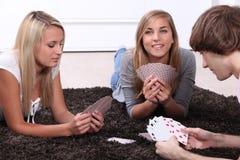 Tre suttna tonåringar spela kort royaltyfria bilder