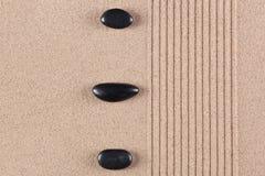 Tre svart pebbles på den krattade sanden Royaltyfria Foton